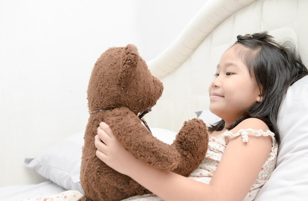 Cute girl is playing with a teddy bear