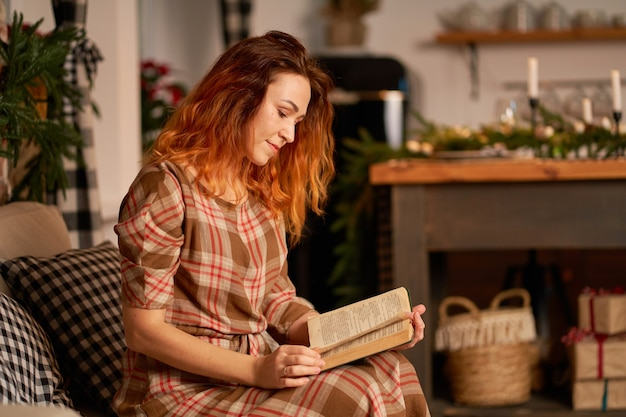 A cute girl is reading a book in a warm and cozy atmosphere. relaxation and privacy concept.