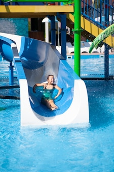 Cute girl is riding water slide child spends sunny summer day in water park at tropical resort by sea