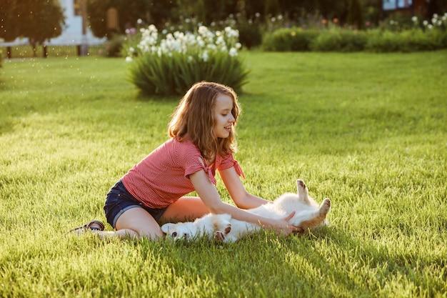 かわいい女の子は、緑の芝生で夏の外で彼女のコーギーペンブローク犬と一緒にトレーニングしています。女の子は彼女の犬をかわいがります。