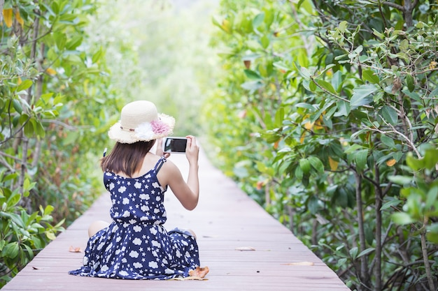 Cute girl is traveling on wooden -walkway in mangrove forest.