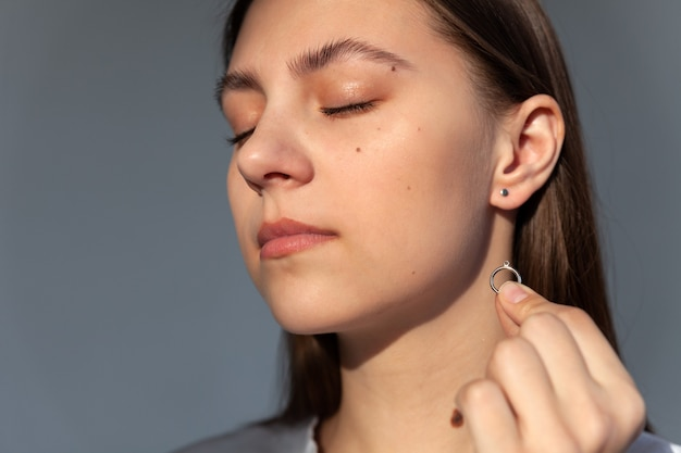 Симпатичная девушка, ювелирная модель, держит и рекламирует современные серебряные круглые серьги в минималистском стиле