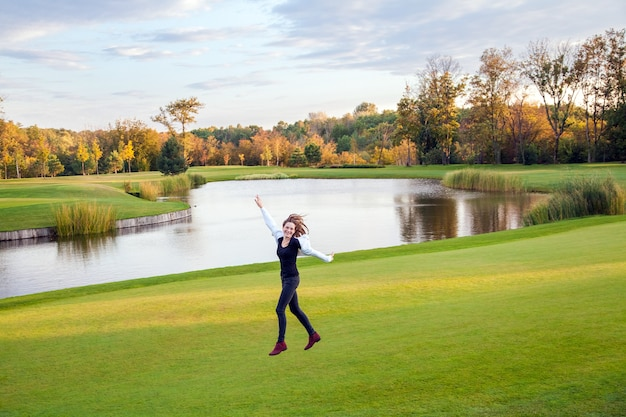 ゴルフ場の緑の芝生の上をジャンプして走っているかわいい女の子。屋外撮影、秋。良い晴れた日