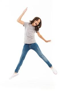 Милая девушка прыгает изолированной на белой стене.