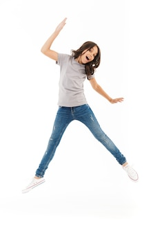 Cute girl jumping isolated on white wall.