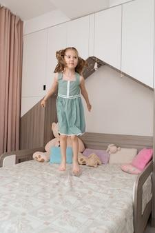 방에 침대에 점프 귀여운 소녀