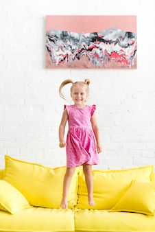Cute girl jumping on yellow sofa
