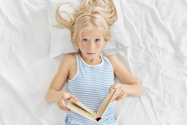 本を手に持って、ベッドに横たわっている間に面白い話を読んで、予期しない結末に驚かされているかわいい女の子。
