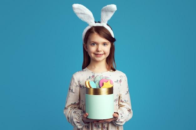 Милая девочка, держащая коробку с печеньем, в кроличьих ушах и милом платье Premium Фотографии