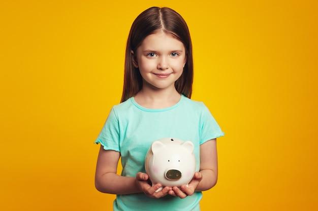 Cute girl kid holding money box in shape of pig isolated over yellow