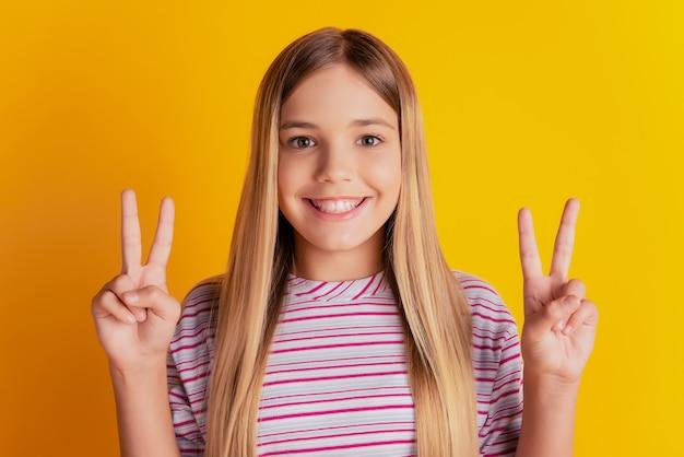 Симпатичная девочка-ребенок делает v-знак на желтом фоне