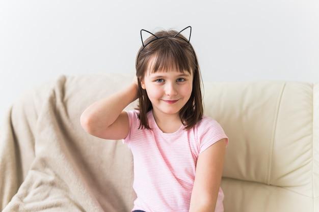 소파에 앉아 고양이 귀를 가진 귀여운 여자 꼬마. 어린이와 어린 시절 개념.
