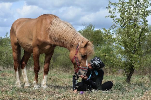 自然の背景で彼女の馬にキスするかわいい女の子
