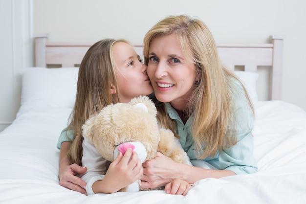 かわいい女の子は彼女の笑顔の母にキス