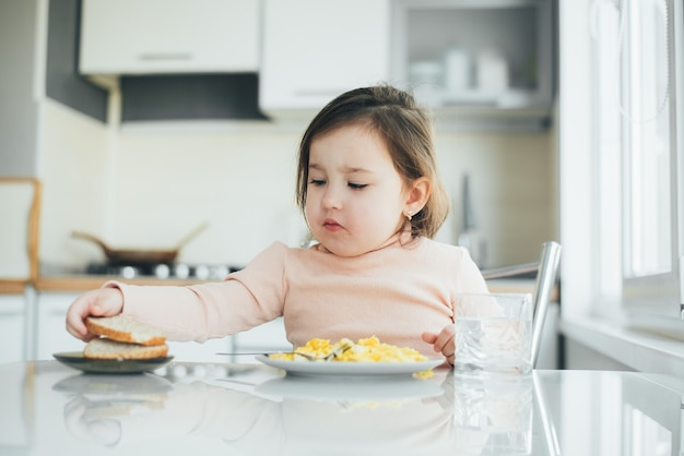 A cute girl in the kitchen is eating bread and an omelet