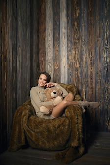 Cute girl in knee socks and sweater with teddy bear in her hands sitting in armchair in wooden room.