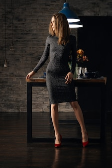 Cute girl in knitted dress standing in dining room near served table