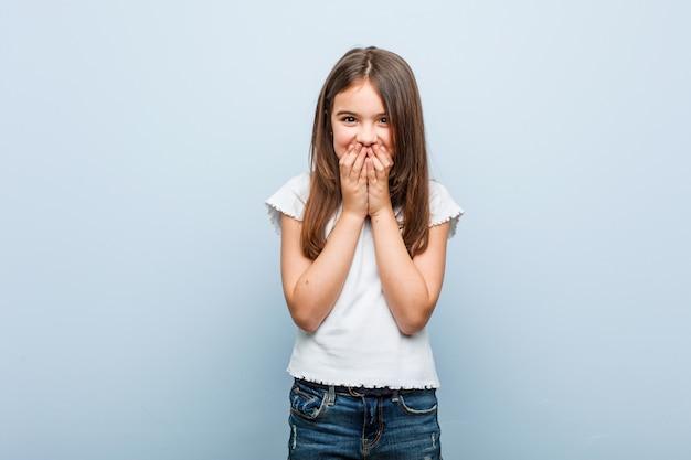 手で口を覆っている、何かについて笑っているかわいい女の子。