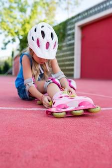 晴れた日に公園でローラーブレードに乗ることを学ぶかわいい女の子