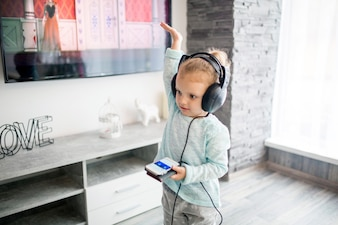 Cute girl listening to music and dancing