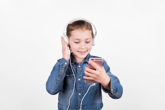 Cute girl listening to music and using smartphone