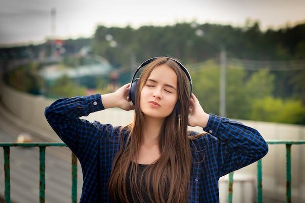 街の通りでヘッドフォンで音楽を聴いているかわいい女の子