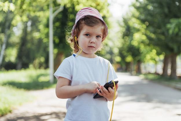 Милая девушка слушает музыку в наушниках на открытом воздухе