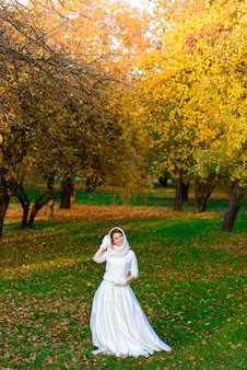 Cute girl in long white wedding dress posing in rural path among autumnal trees in forest in golden hour atmosphere.