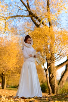 Cute girl in long white wedding dress posing in rural path among autumnal trees in forest