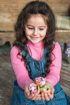 Cute girl looking at broken eggs with flowers