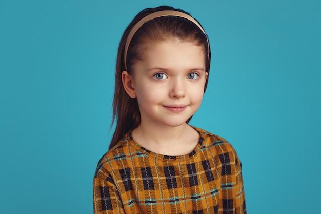 Симпатичная девушка смотрит мирно и стоит изолированно на синем фоне
