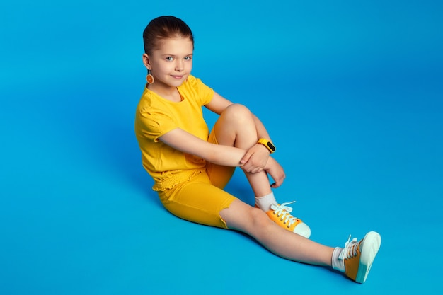Cute girl looks at camera with smile sits on floor against blue background