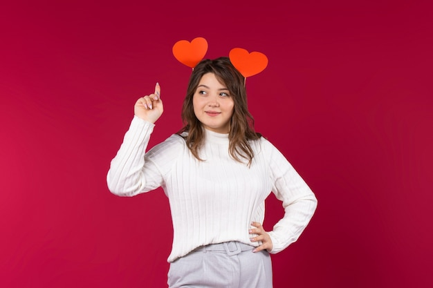 Cute girl looks to the side with index finger to the top. handmade hearts in the hair.