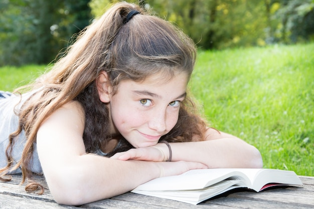 Cute girl lying on a bench in a park reads a book