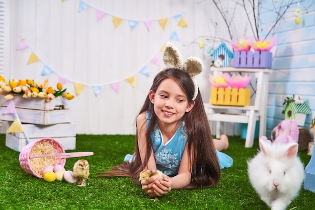 Cute girl lying on grass with easter eggs. chickens and a rabbit walk on grass.