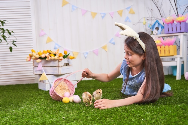 Cute girl lying on the grass with easter eggs. chickens walk on the grass.