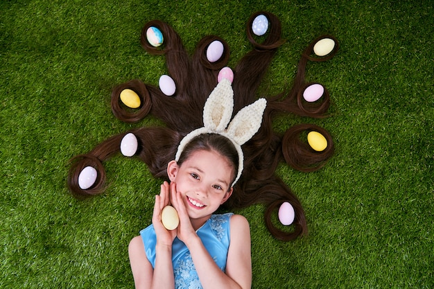 Cute girl lying on the grass with easter eggs. easter eggs are in her hair.
