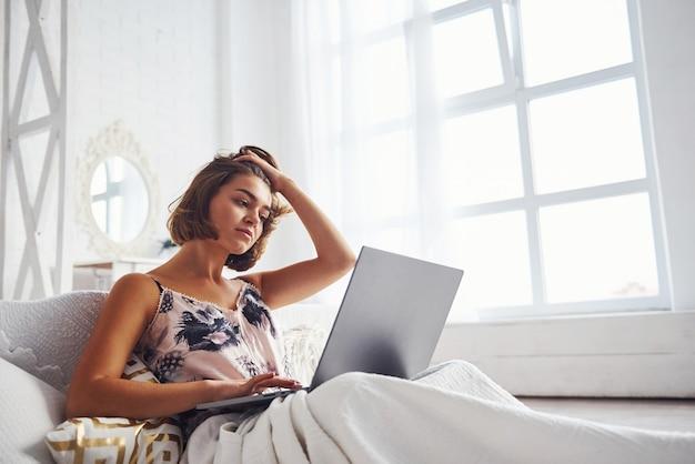 Милая девушка, лежа на кровати с ноутбуком в спальне в выходные дни.