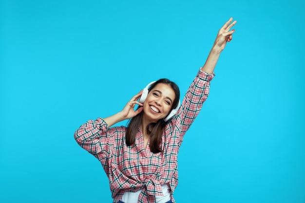 Милая девушка делает жест мира с поднятой рукой, слушает музыку в наушниках