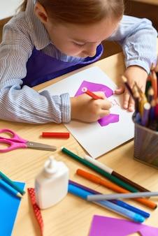 Милая девушка, делающая открытку ручной работы для мамы