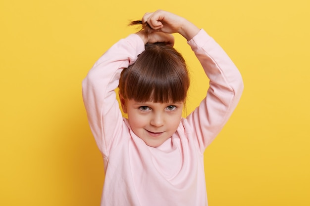 그녀의 머리의 조랑말 꼬리를 만드는 귀여운 소녀, 그녀의 손을 올리는, 카메라를 바라보고, 분홍색 캐주얼 스웨터를 입고, 노란색 배경 위에 고립 된 서있는 작은 매력적인 여자 아이가 헤어 스타일을 만듭니다.