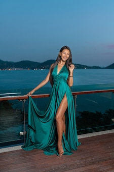 Cute girl of mixed race posing on the terrace in a dress in the colors of the sea wave holding the hem of the dress in her hand