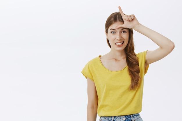 額に敗者のサインを示す人をあざけるかわいい女の子