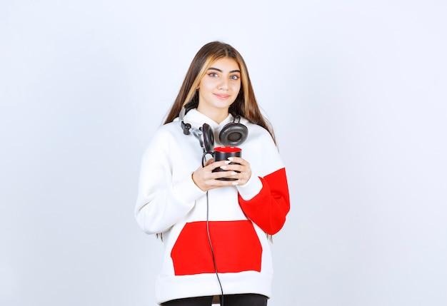 Un modello di ragazza carina in piedi con le cuffie e con in mano una tazza di bevanda