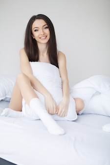 Cute girl in the morning on a white bed with a pillow