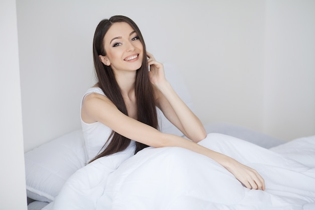 Cute girl in the morning on a white bed