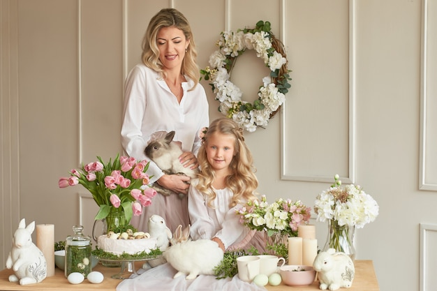 Cute girl and mother playing with rabbit in decorated room