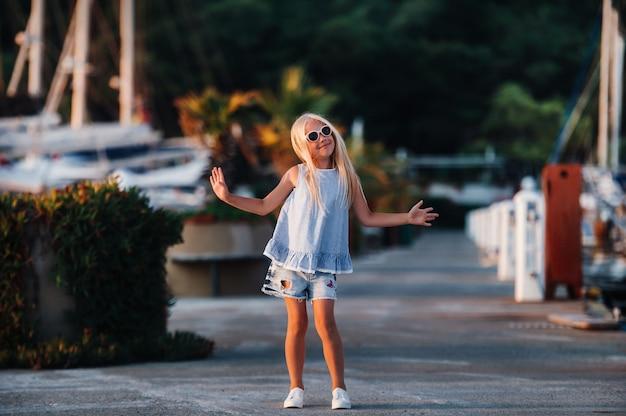 여름에 요트 근처 귀여운 소녀. 가족 휴가를 위해 아이와 함께 여행, 모험, 보트 여행. 선원 스타일의 아동복, 해양 패션.