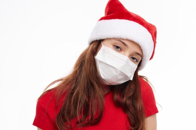 Милая девушка новогодняя одежда медицинская маска образ жизни светлый фон. фото высокого качества
