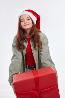 Симпатичная девушка новогодний подарок улыбка санта шляпа праздник веселье радость. фото высокого качества